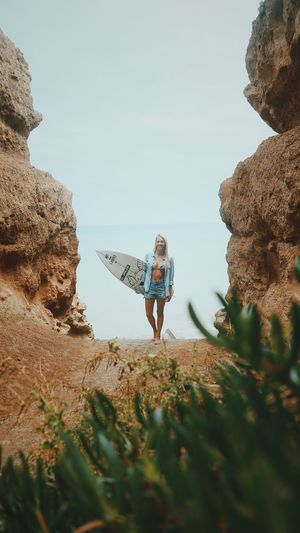 Portrait Of Young Woman With Surfboard Standing At Beach