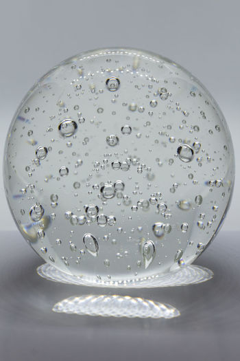 Close-up of water drops on glass against white background