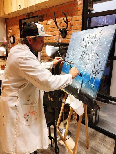 Side View Of Artist Painting In Workshop