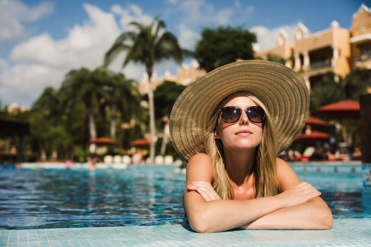 A beautiful woman relaxing in the pool on a sunny day. Glasses Sunglasses Water Portrait Fashion Leisure Activity One Person Swimming Pool Pool Young Adult Real People Headshot Young Women Lifestyles Focus On Foreground Day Clothing Hat Hair Hairstyle Beautiful Woman Outdoors Sun Hat Tropical Climate