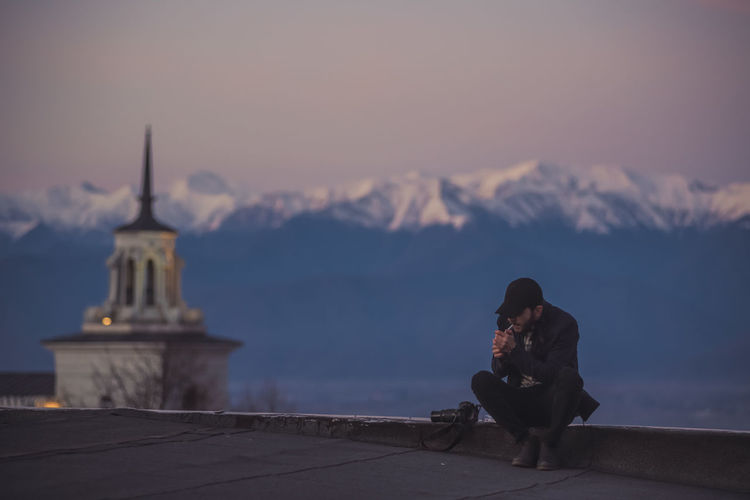 Man Smoking While Sitting Against Snowcapped Mountain During Sunset