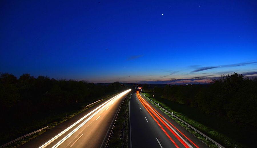 Light Trails On Road Against Sky At Dusk