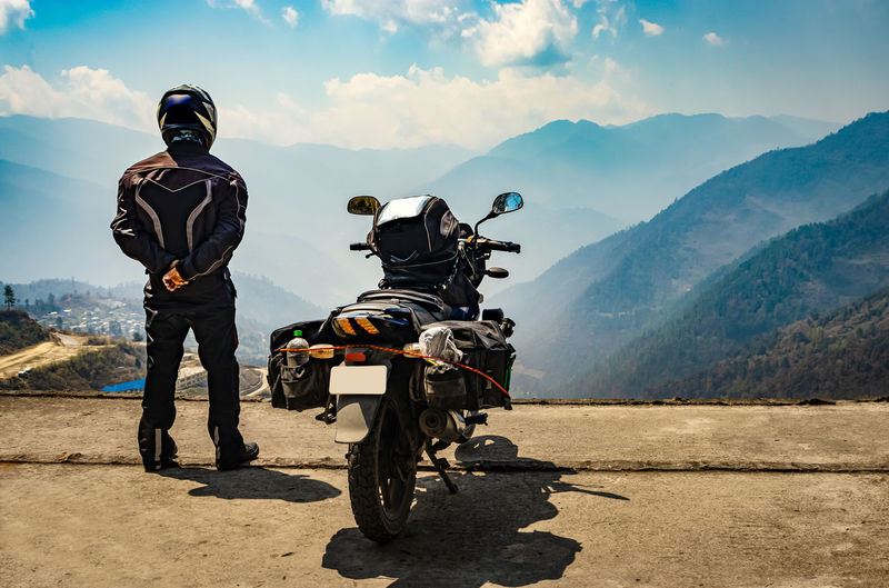 Man motorcyclist watching valley from hill top with his loaded motorcycle and pristine natural view
