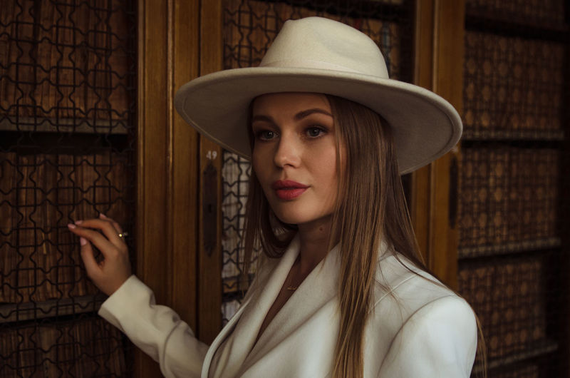 Portrait of beautiful young woman wearing hat and blazer by wall