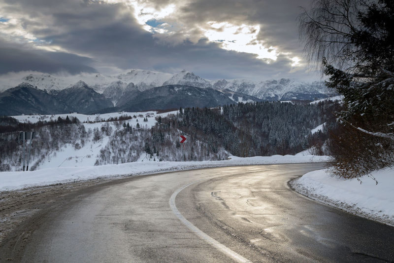 Road by mountains against sky during winter