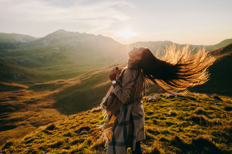 Side view of woman tossing hair while standing on mountain against sky during sunset