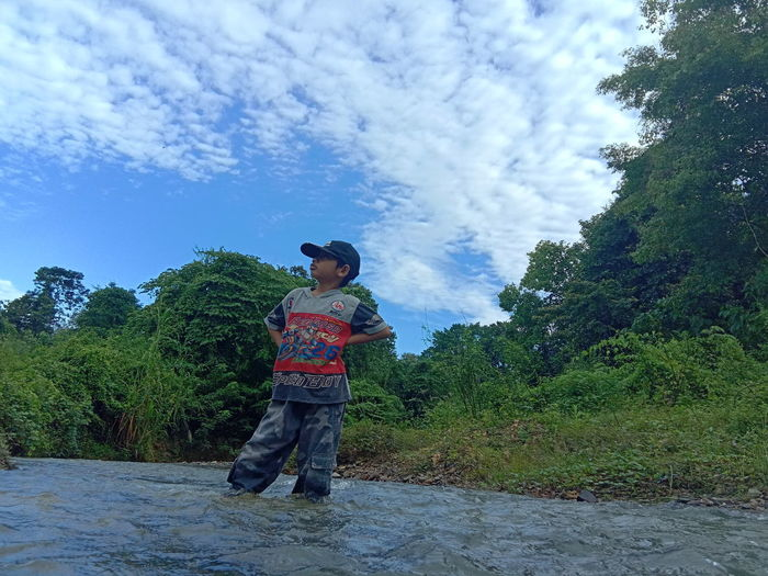 A Boy River River View Jungle Sky And Clouds Tree Full Length Spraying Men Standing Water Sky Cloud - Sky