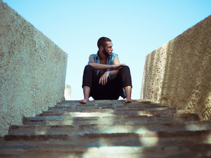 Young Man Sitting On Steps Against Clear Sky
