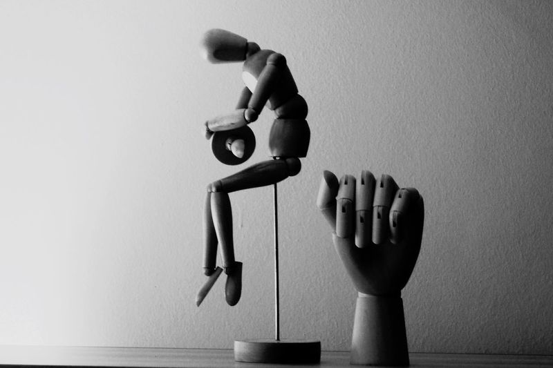 Wooden figurine on table against wall