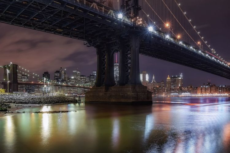 Low angle view of manhattan and brooklyn bridge over east river at night