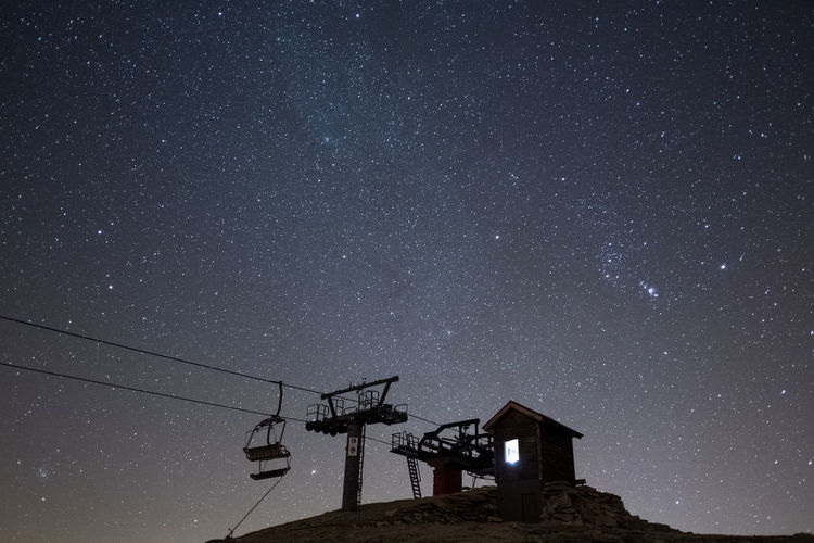 Low angle view of ski lift against sky at night