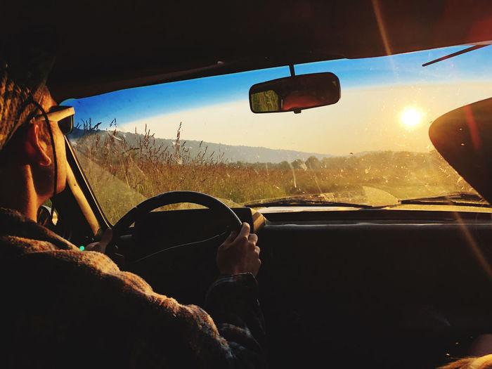 Man seen through car windshield during sunset