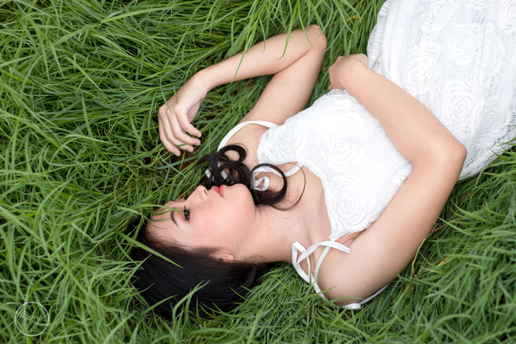 Beautiful Woman Childhood Day Grass Green Color High Angle View Leisure Activity Lifestyles Lying Down Lying On Back Nature One Person Outdoors People Real People Relaxation Sleeping Young Adult Young Women