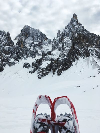 Low Section Of Person Wearing Ski Boots On Snowcapped Mountain