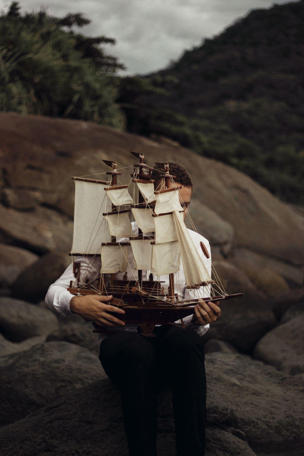 Man holding ship toy on land
