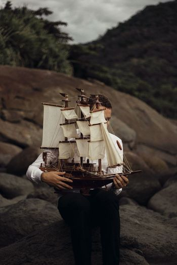 Man holding ship toy on land