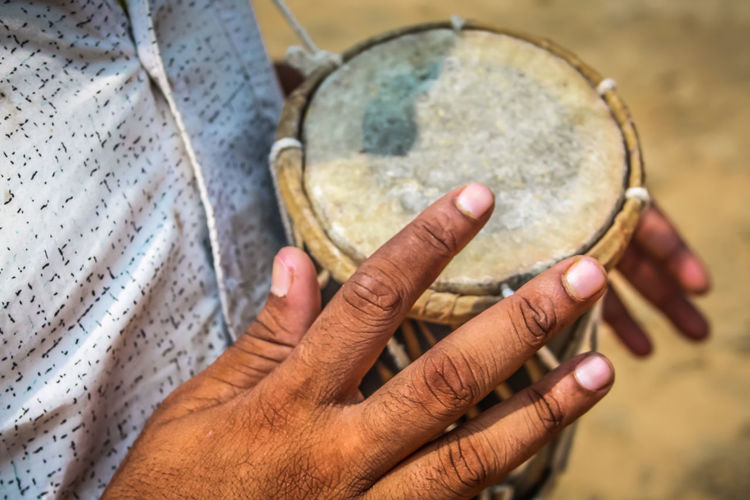Midsection of man playing drum