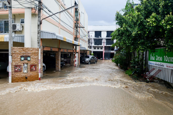 SRIRACHA, THAILAND - October 29 : Flood after heavy rain in Sriracha, Chonburi, Thailand on 29 October 2016 Architecture Building Building Exterior Built Structure City City Climate Day Flood No People Outdoors Road Street Town Tree Water Waterway Wet