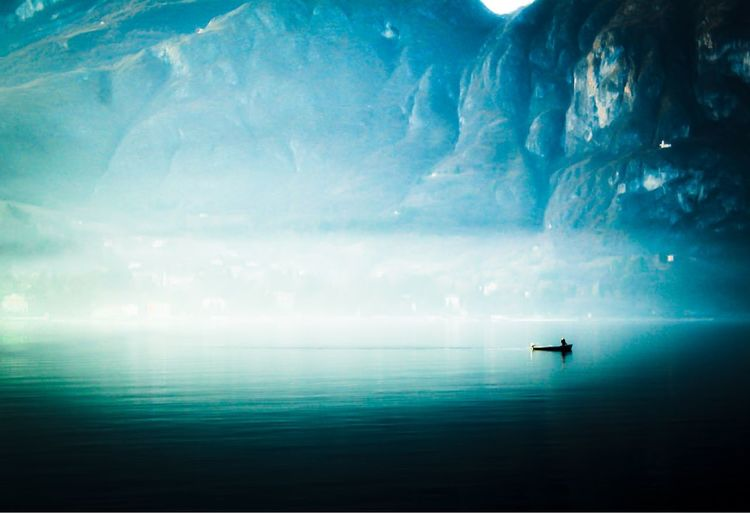 Silhouette man in sea against sky