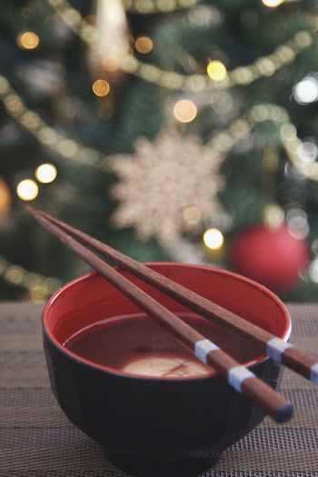 Close-up of bowl with chopsticks against christmas tree on table