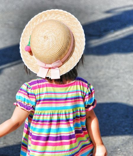 Midsection of child standing by hat