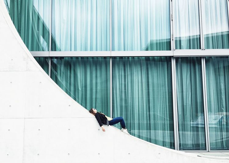 Woman lying on wall against building