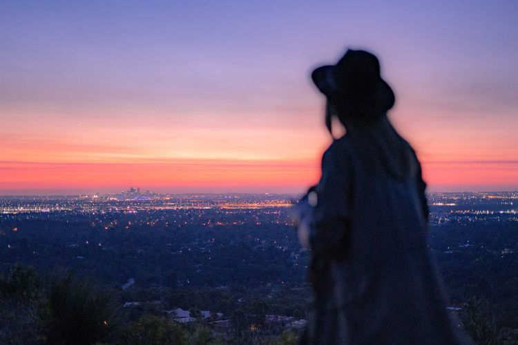 Woman looking at illuminated cityscape against sky during sunset