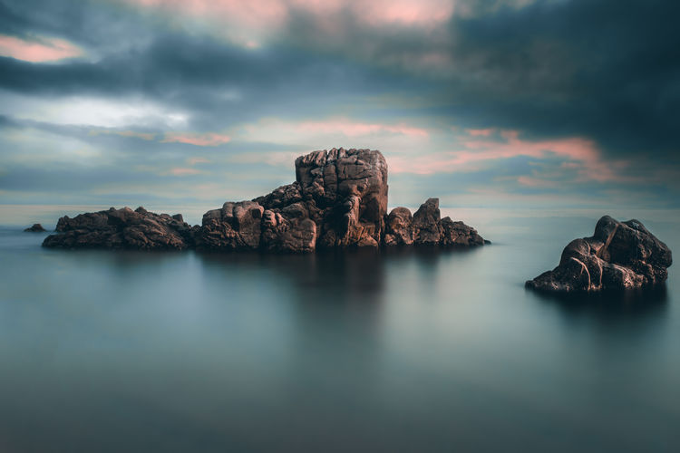Rock formation in sea against dramatic sky