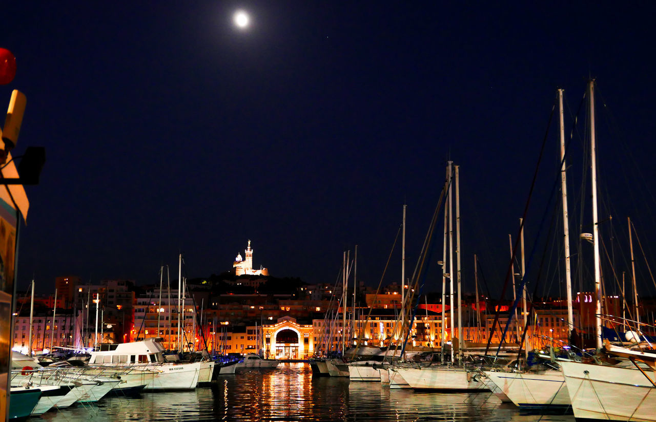 nautical vessel, transportation, water, sky, moored, mode of transportation, night, harbor, illuminated, architecture, sailboat, no people, nature, mast, clear sky, pole, building exterior, moon, built structure, yacht, full moon, port, marina, luxury, bay