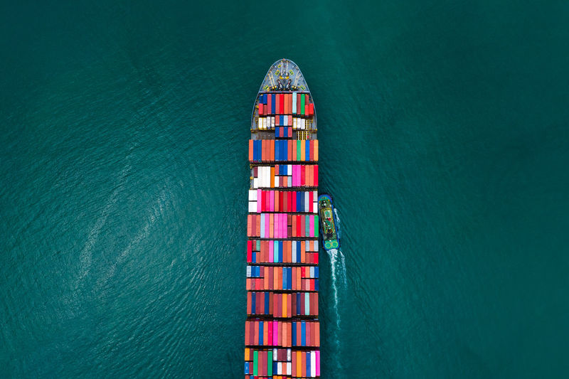 High angle view of shipping containers sailing export import international on the green sea
