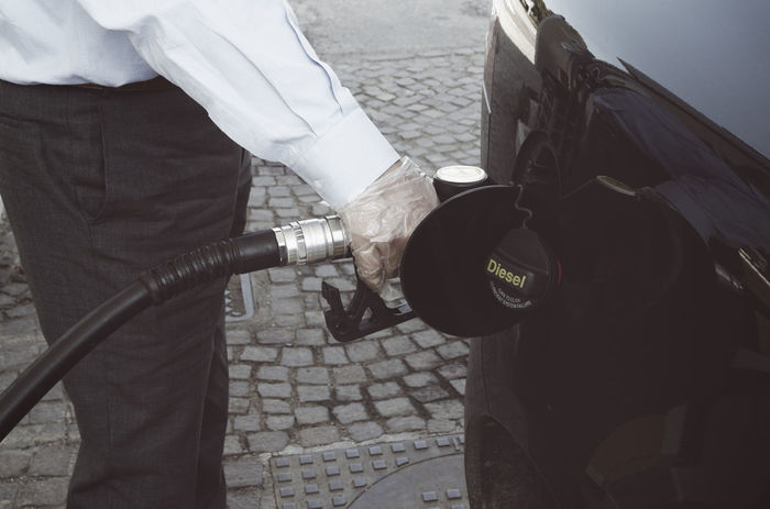 A man fills his car with Diesel fuel Adult Car Diesel Disposable Fill Fuel Gas Station Gasoline Gloves Holding Human Hand Low Section Man Nozzle One Person Outdoors People Petrol Petrol Station Pump Real People Refueling Side View Vehicle