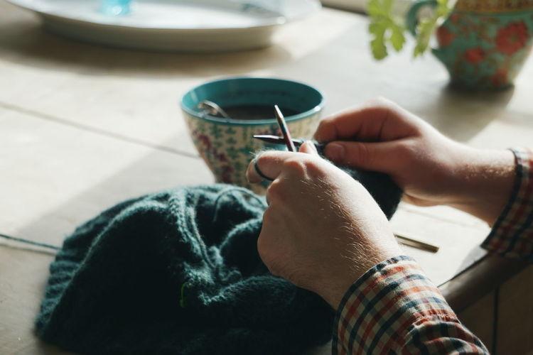 Close up of young man knitting at home