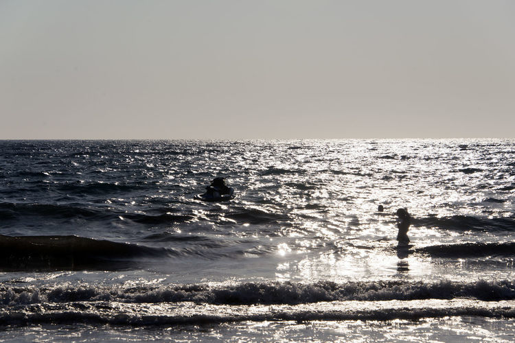 SILHOUETTE OF People playing, swimming in the waves in the island of Patmos, Greece in summer time Beach Beauty In Nature Clear Sky Copy Space Horizon Horizon Over Water Land Men Motion Nature Outdoors Real People Scenics - Nature Sea Silhouette Sky Tranquil Scene Tranquility Two People Water