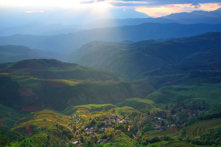 Beautiful landscape of village on mountain range with beam light in morning at Hongtudi in Dongchuan, Yunnan, Kunming of China Mountain Scenics - Nature Beauty In Nature Tranquil Scene Tranquility Mountain Range Environment Landscape Sky Non-urban Scene Nature Fog No People Idyllic Sunlight Day Plant Outdoors Sunbeam Sun China Village
