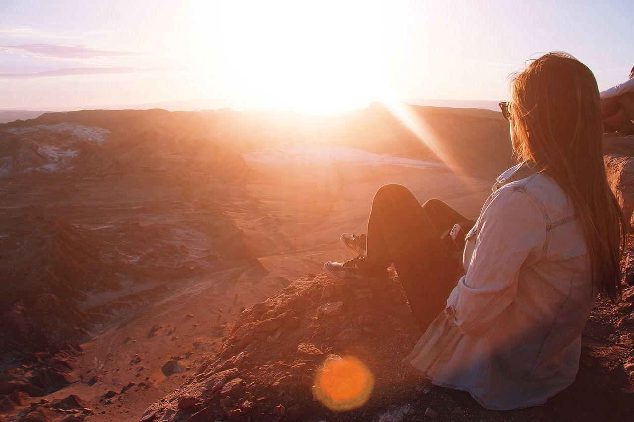 Rear View Of Woman Sitting On Cliff Against Sky During Sunset