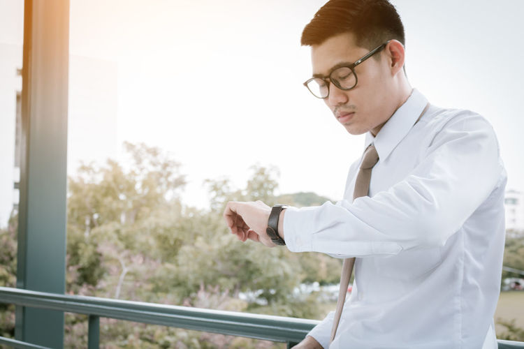 Businessman checking time in wristwatch against sky