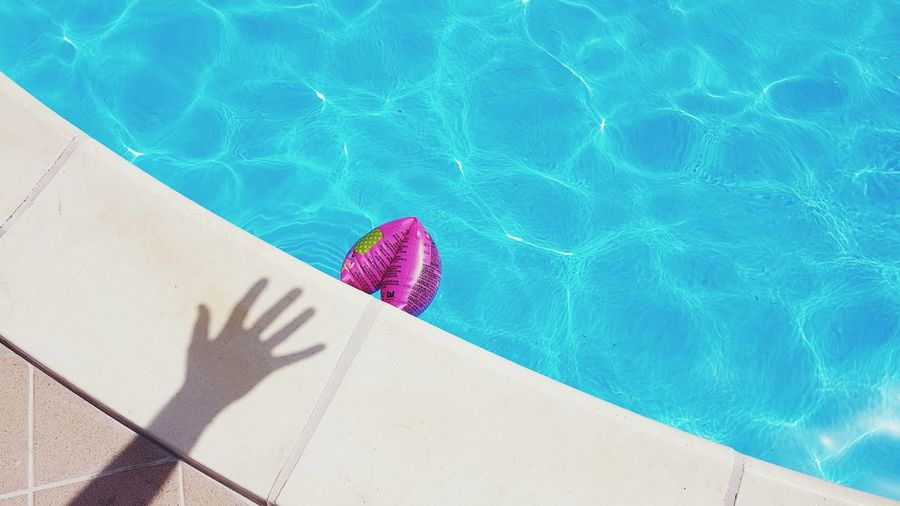 Shadow of hand on poolside