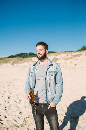 Young Man Holding Beer Bottle While Standing At Beach Against Clear Sky