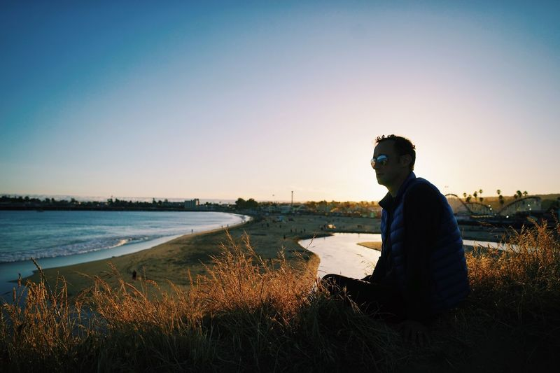 Side view of man sitting on grass by beach