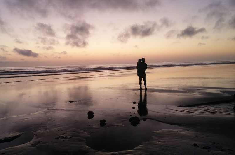 Person holding a child on beach at sunset