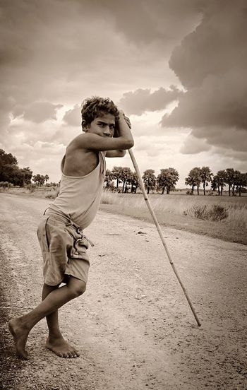 Portrait of boy with stick standing on footpath against sky