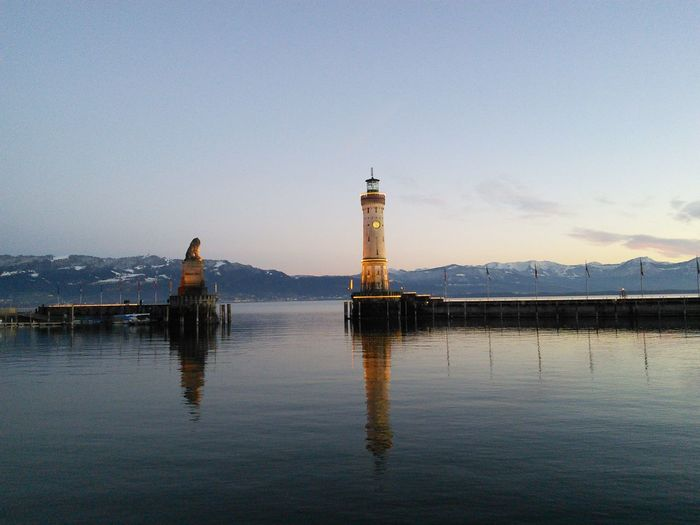 Reflection of lindau lighthouse on lake against clear sky