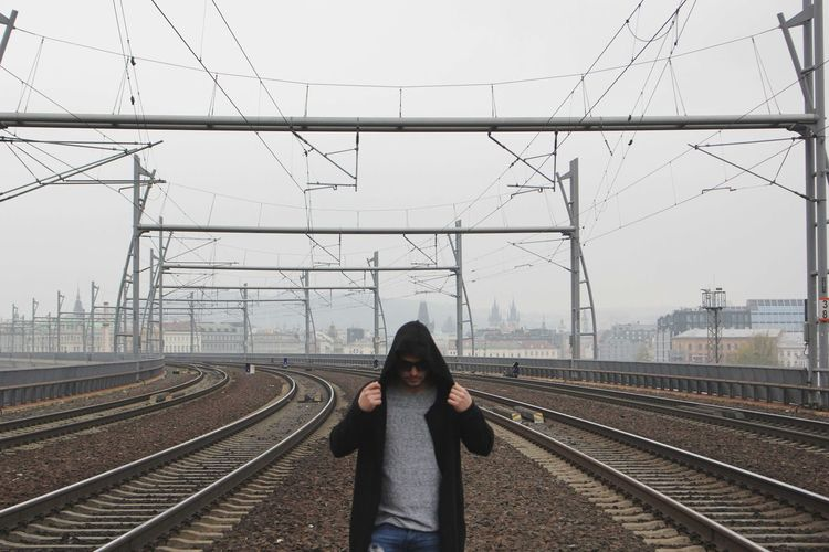 Man Standing On Railway Tracks Against Clear Sky
