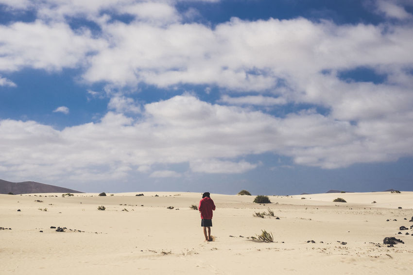 Alone man walking in the desert of Fuerteventura Canary Islands Adventure Arid Climate Beauty In Nature Cloud - Sky Day Desert Full Length Landscape Leisure Activity Lifestyles Nature One Person Outdoors People Rear View Red Jacket Sand Sand Dune Scenics Sky Solitude Standing Tranquility Walking