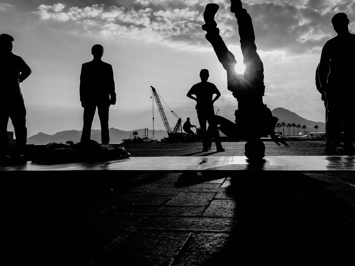 Silhouette people by sea against sky