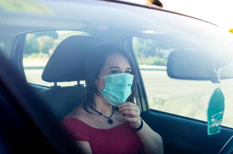 View of woman wearing flu mask sitting in car