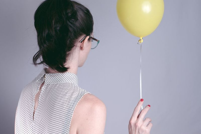 Rear view of woman holding balloons against gray background