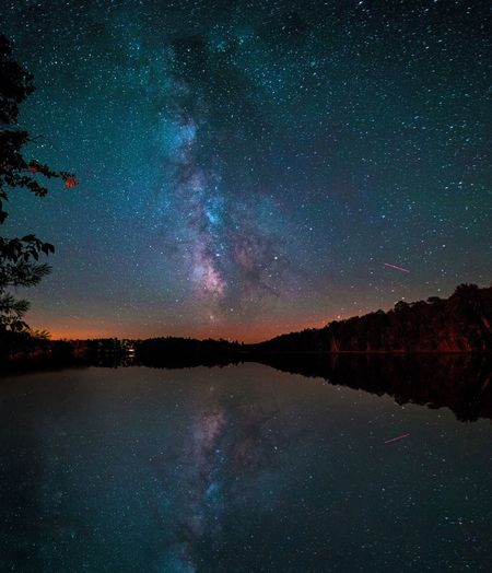 Scenic view of galaxy reflection in lake against sky at night