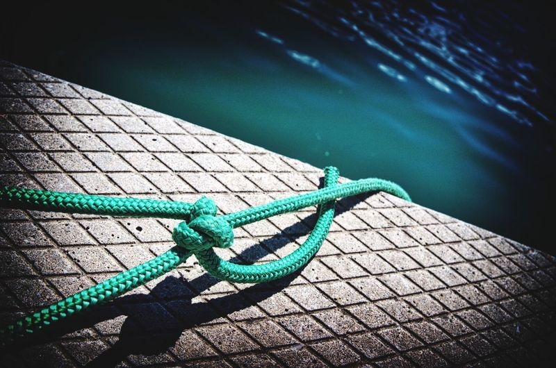 Close-up of rope on retaining wall by river