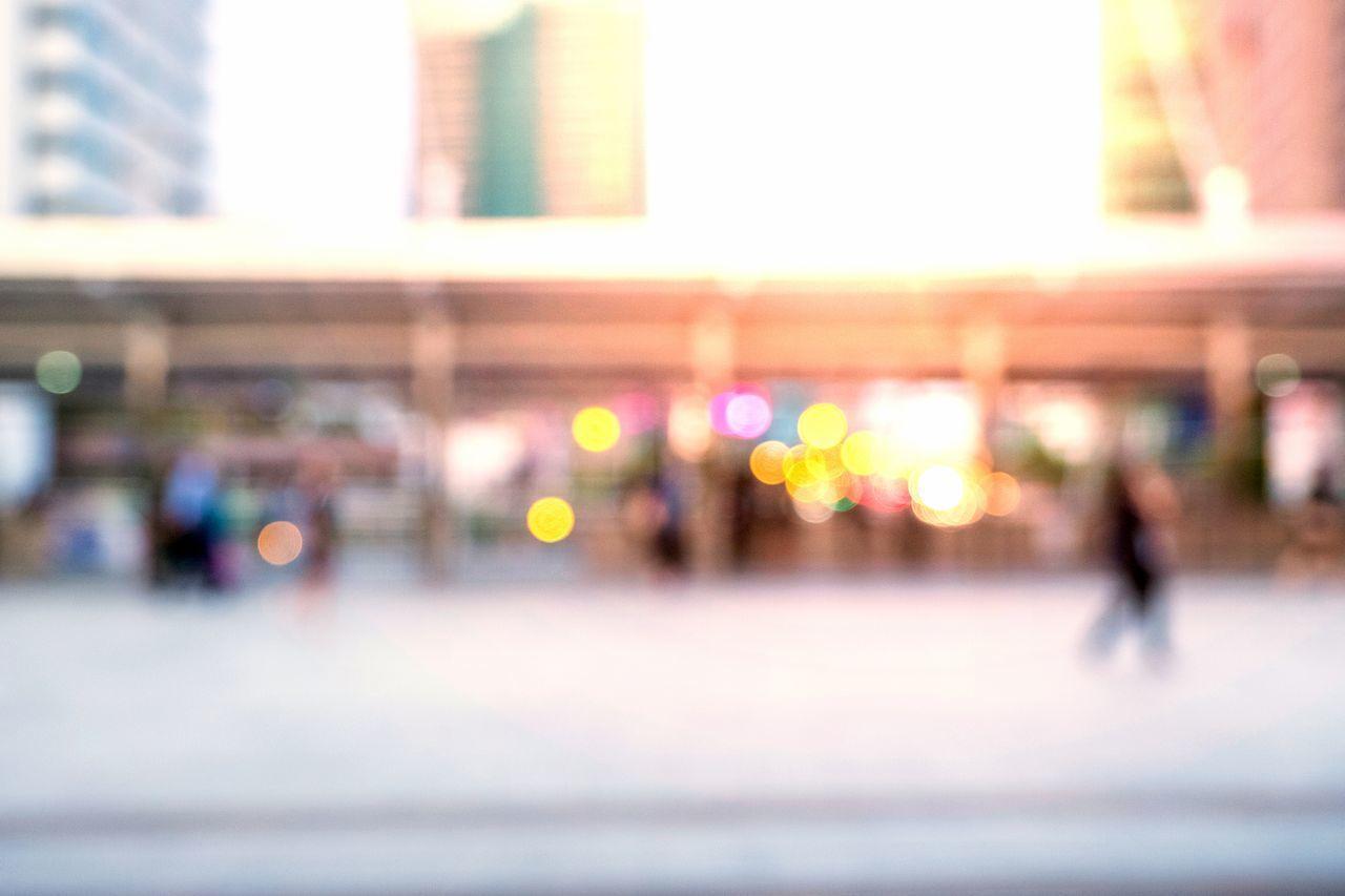 DEFOCUSED IMAGE OF MAN WALKING ON ILLUMINATED STREET